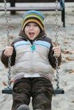 Kind auf einem Schwingen Stockbild