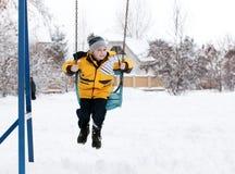 Kind auf einem Schwingen im Winter Stockfotos
