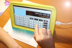 Kind auf einer Laptop-Computer macht Berechnungen auf dem Hintergrund des Desktops stockbilder