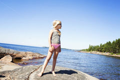 Kind auf felsigem Strand in Schweden Lizenzfreies Stockfoto