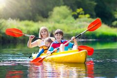 Kind auf Kajak Kinder auf Kanu Sommerkampieren stockfotografie