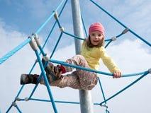 Kind auf kletterndem Rahmen Stockfotos