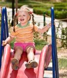 Kind auf Plättchen im Spielplatz. Im Freienpark. Stockbild