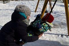 Kind auf Schwingen im Winter stockfotografie