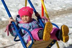 Kind auf Schwingen im Winter Stockfoto