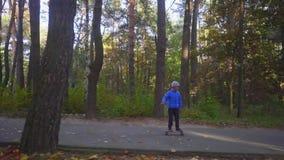 Kind auf Skateboardjungenfahrt auf den Rochen im Freien im Herbstpark