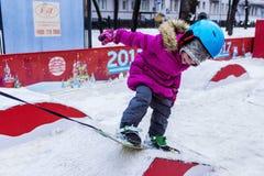 Kind auf Snowboard Stockbild