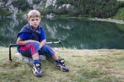 Kind auf Stein mit dem Wandern der Stange Stockfotografie