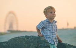 Kind auf Strand mit Ferris Wheel Behind Stockbild