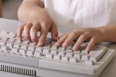 Kind auf Tastatur lizenzfreie stockbilder