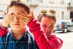 Kind bedeckt seine Augen mit seinem Bruder, Porträt lizenzfreies stockbild