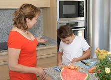 Kind befleckt Hemdwann vorbereitet das Mittagessen mit seiner Mutter lizenzfreies stockfoto