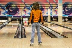 Kind behält geworfenen Ball im Bowlingspiel im Auge lizenzfreie stockfotos
