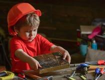 Kind beim dem netten Spielen des Sturzhelms als Erbauer oder Reparaturhauer, der Reparatur oder handcrafting Handcrafting Konzept lizenzfreie stockfotos