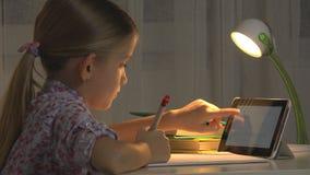 Kind benutzt Tablet für das Studieren, das Mädchen, das Hausarbeit in Nachtinternetnutzung schreibt stockfotografie