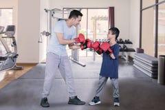 Kind bereit, mit seinem Vater in der Turnhallenmitte zu kämpfen lizenzfreies stockfoto