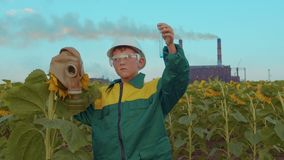 Kind in beschermend masker met de installatiezonnebloem op het bedrijf als achtergrond ecologische crisisfoto stock video