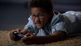 Kind betonte emotional das Spielen des aktiven Spiels auf Konsole, Schadengesundheitssucht lizenzfreie stockbilder