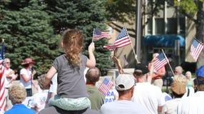 Kind bewegt amerikanische Flagge an der Sammlung wellenartig, um unsere Grenzen zu sichern Lizenzfreie Stockfotografie