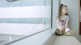 Kind bij de luchthaven dichtbij het venster die vliegtuigen bekijken en op tijd van vlucht wachten stock videobeelden