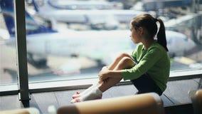 Kind bij de luchthaven dichtbij het venster die vliegtuigen bekijken en op tijd van vlucht wachten stock video