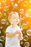 Kind blazen zeepbels Jongen met bal Jong geitje blazende bellen o stock afbeeldingen
