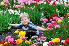 Kind in bloemen royalty-vrije stock foto