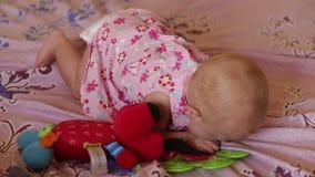 Kind blond im Kleid, das auf Bett liegt stock footage