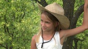 Kind in Boomgaard, Landbouwer Girl Face Relaxing Openlucht in Aard, Peinzend Jong geitje 4K stock videobeelden