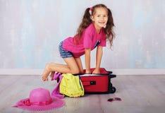 Kind in borrels en een roze T-shirt die op vakantie gaan Stock Afbeeldingen