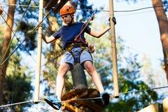 Kind in bosavonturenpark Het jonge geitje in oranje helm en blauwe t-shirt beklimt op hoge kabelsleep Behendigheid vaardigheden e stock fotografie