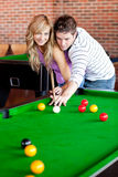 Kind boyfriend teaching pool to his girlfriend Royalty Free Stock Photos
