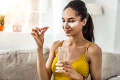 Kind brunette girl looking at healthy vitamin royalty free stock image