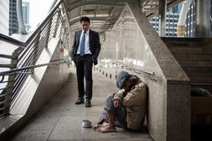 Business man look at Homeless in city. Kind Business men with black suit look at sad beggar men or old homeless guy at city walk in urban town. Poverty and Royalty Free Stock Image