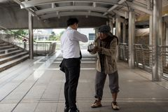 Businessman give money to old homeless. Kind Businessman giving money to old beggar or homeless guy at city walk in urban town. Poverty and social issue concept Royalty Free Stock Photos