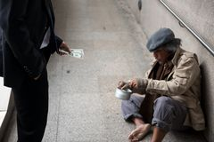 Business man give money to homeless man. Kind Businessman hold dollar bill money to donate to old beggar or homeless man at city walk in urban town. Poverty and Royalty Free Stock Photo
