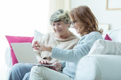 Kind carer teaching old lady. Picture of kind carer teaching old lady to use laptop Royalty Free Stock Photos
