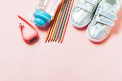 Kind-clothesand Studienmaterial: sneackers, Bleistifte, Flasche Wasser und Elektron gps-Uhren stockbilder