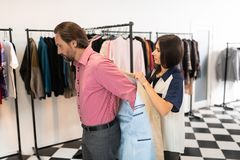 Kind consultant assisting a customer during trying on a blazer. Assisting during fitting. Kind good-looking attractive lovely showroom consultant assisting a stock photo
