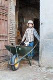Kind d.w.z. dragend een kat in de kruiwagen Royalty-vrije Stock Fotografie