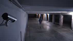 Kind of dangerous person walking at night on an underground passage in the background of a surveillance camera. View of dangerous man walking at night stock footage