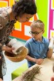Kind, das über Anlagen an einer Werkstatt lernt Stockbilder