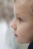 Kind, das Abflussrinne das Fenster schaut. Lizenzfreies Stockfoto