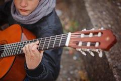 Kind, das Akustikgitarrenahaufnahme spielt Stockfotografie