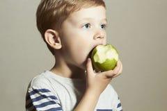 Kind, das Apple isst Kleiner hübscher Junge mit grünem Apfel Biokost Corn Flakes Früchte Stockfoto