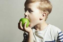 Kind, das Apple isst Little Boy mit grünem Apfel Biokost Corn Flakes Früchte Lizenzfreie Stockfotografie