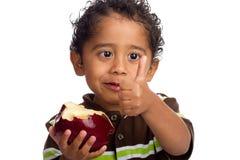 Kind, das Apple isst und Daumen aufgibt Lizenzfreie Stockfotografie
