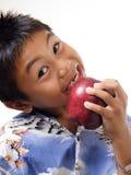 Kind, das auf Apfel beißt lizenzfreie stockfotos