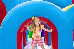 Kind, das auf aufblasbarem Spielplatz spielt Stockfotografie