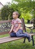 Kind, das auf Bank sitzt Stockfotografie